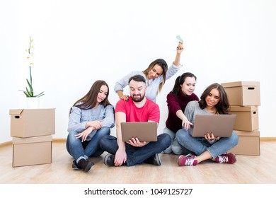 Friends after moving to a new house choose furniture in the online store sitting on the floor with boxes of things