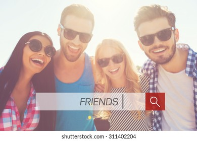 Friends are always near. Low angle view of four cheerful young people bonding to each other and looking at camera while standing against sky