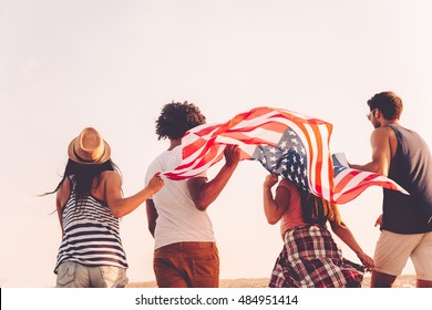 Friends with American flag. Rear view of four young people carrying american flag while running outdoors