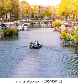 Friends around with their boat along the Amsterdam canals, Holland
