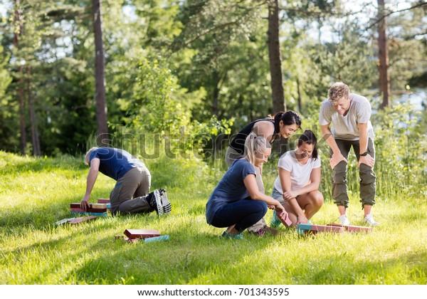 Friends Arranging Building Blocks On Grassy Field