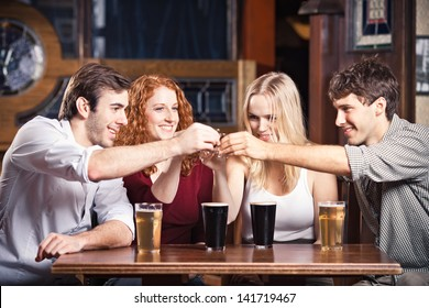 Friends at a bar cheering some shot glasses.
