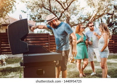 Friends at bbq party enjoying drinks and having a good time while cooking