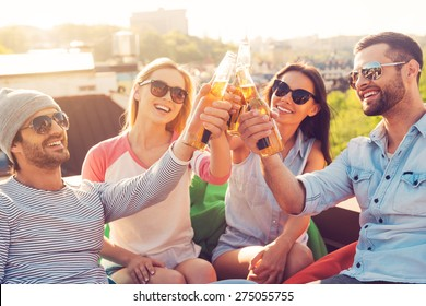 Friends and beer. Four young cheerful people cheering with beer and smiling while sitting at the bean bags on the roof of the building
