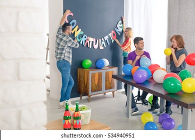 "Friends blowing colorful balloons, man and woman holding ""congratulations"" banner"