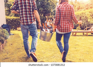 Friends bring cold beer to a garden party. Bucket of ice and bottles of beer