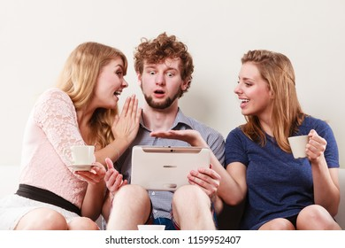 Friends browsing surfing internet on tablet. Young people man and women relaxing at home. Girl whispering to guy ear.