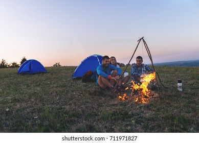 Friends Camping  around Campfire