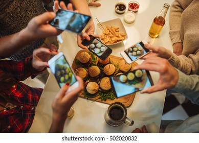 Friends capturing burgers and drinks on the table.
