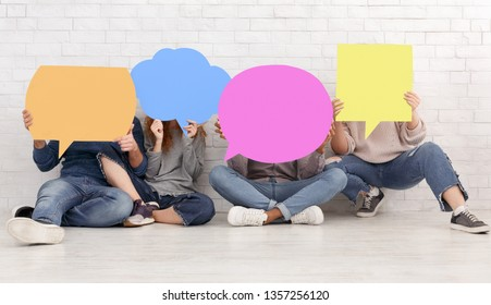 Friends carrying empty speech bubble icons, closing their faces over brick wall