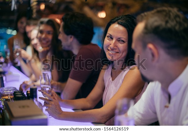 Friends celebrate the New Year at the bar behind the bar. A cheerful company is laughing with glasses of champagne at night. New Year and Christmas in the tropics