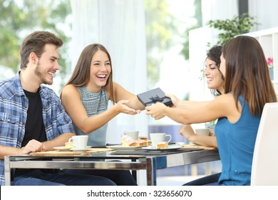 Friends celebrating birthday and giving gift to a girl sitting in a dining room