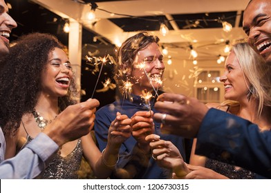 Friends celebrating christmas with bengal lights. Group of elegant women and men celebrating new year's eve outdoor with sparklers. Smiling group of girls and guys with firework sticks outside.