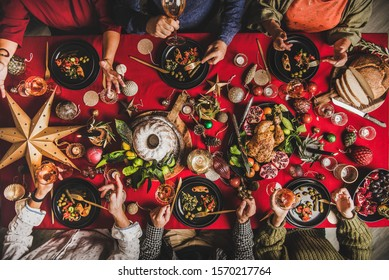Friends celebrating Christmas. Flat-lay of people eating and talking over festive table with red cloth with champagne, roasted chicken, bundt cake, fruits, decorations, top view. Winter holiday party