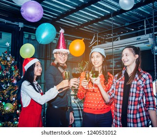 Friends celebrating Christmas or New Year party, cheering with wine, christmas lights decoration background, christmas atmosphere. Close-up of people make good cheer.
