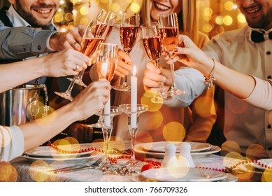 Friends celebrating Christmas or New Year eve. Party table with lights and rose champagne.