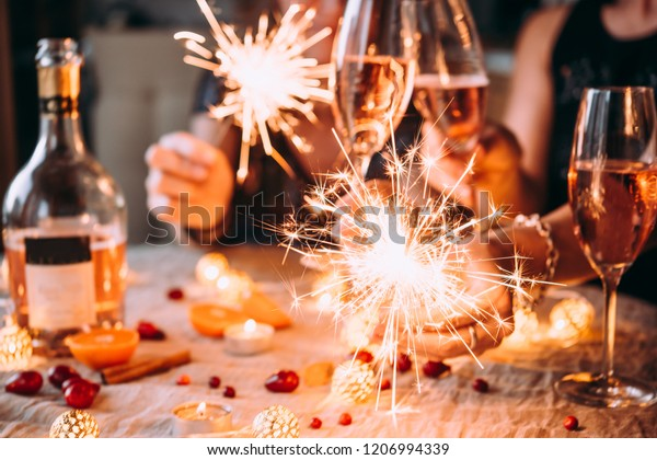 Friends celebrating Christmas or New Year eve party with Bengal lights and rose champagne.
