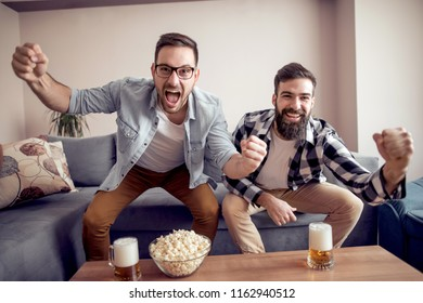 Friends celebrating a goal while watching a soccer game at home with popcorn and beer.