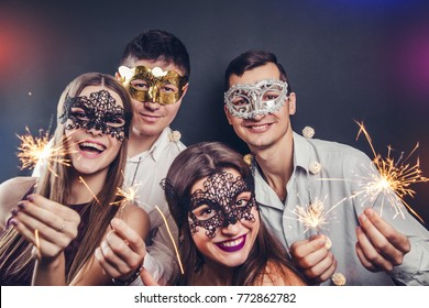 Friends celebrating New Year's eve drinking champagne and lighting up sparklers on masquerade party