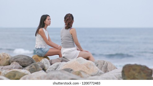 Friends chatting together and sitting beside at the sea