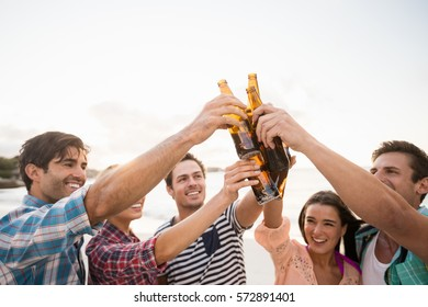 Friends cheering with beer at the beach