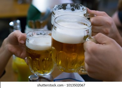 Friends cheering with beer glasses in a pub