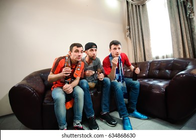 Friends cheering and drinking alcohol while watching soccer match on TV