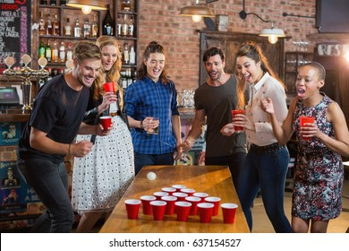 Friends cheering while man playing beer pong on table in bar