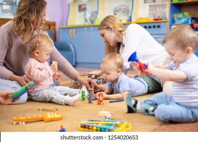 Freunde mit kleinen Kindern, die im Montessori-Zentrum auf dem Boden spielen