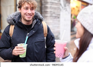 Friends in city drinking bubble tea / pearl milk tea smiling happy and talking in chinatown of Montreal, Quebec, Canada.