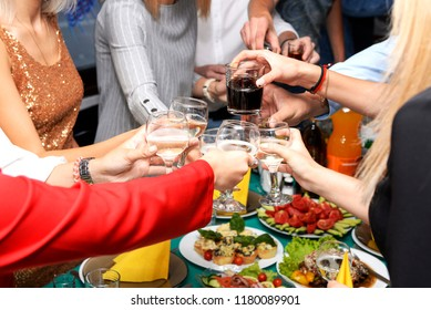 Friends clink glasses with alcohol over the festive table at a party