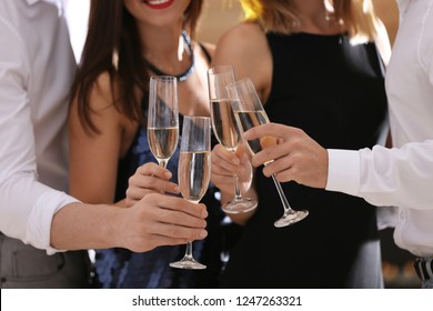 Friends clinking glasses with champagne at party, closeup