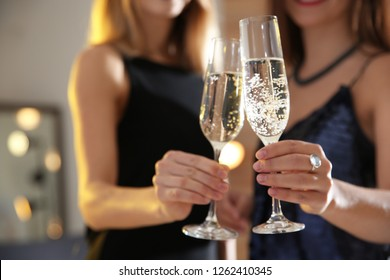 Friends clinking glasses with champagne at party indoors, closeup