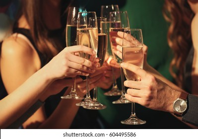 Friends clinking glasses at party, closeup