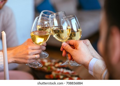 Friends clinking with glasses of wine.