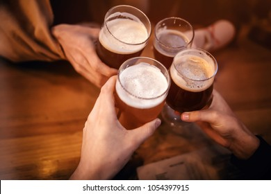 friends clinking and toasting with delicious craft beer in bar. group of people cheering and enjoying a beer in pub. hands holding glasses of beer. leisure and friendship  concept