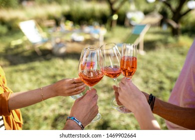 Friends clinking wine glasses in the garden with beautifully decorated dinning place, close-up view