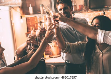 To the friends! Close-up of cheerful young people cheering with champagne flutes and looking happy while having party at home