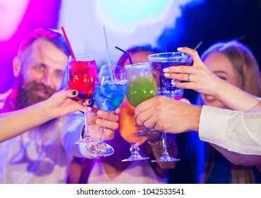 Friends with cocktails drinks at a party.