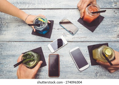 friends with cocktails. Four hands holding cocktails. Smart phones are down on the table. taking a break from technology and enjoying life