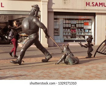 Friends from the comic.  Dundee, Scotland - 18 February 2019 Artistic statue of Desperate Dan and Beano Minnie, a British comic book character in the center of Dundee.