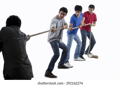 Friends competing in game of tug of war together over white background