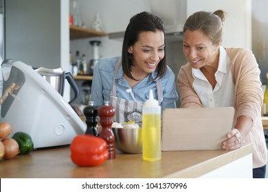 Friends cooking together with kitchen robot and tablet