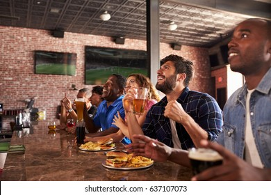 Friends At Counter In Sports Bar Watching Game