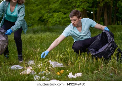 Friends crouching with bag picking up trash doing plogging.Plogging concept. Boy and girl picking up trash from the forest. They collecting the litter in garbage bag