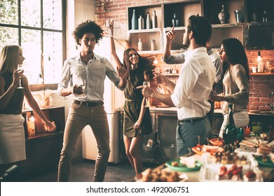 Friends dancing. Cheerful young people dancing and drinking while enjoying home party on the kitchen