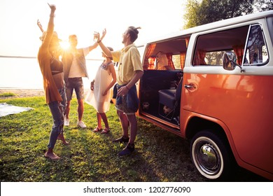 Friends dancing in the light of sunset. summer holidays, road trip, vacation, travel and people concept - smiling young hippie friends having fun over minivan car