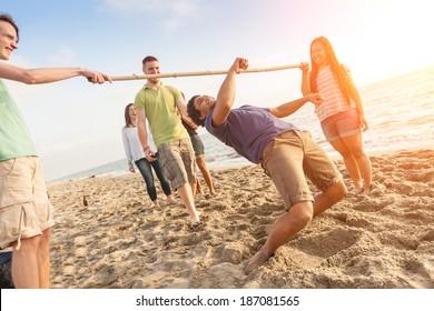 Friends Dancing Limbo at Beach