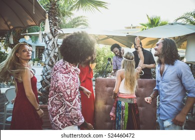 Friends dancing in a lounge bar, with dj set