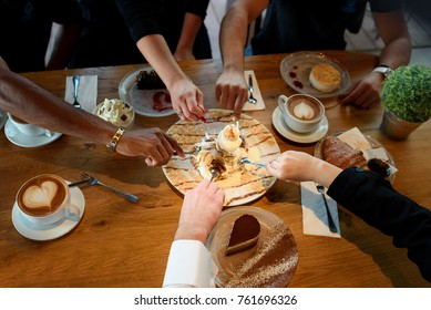 Friends with desserts and coffee, close up.Happy couple sitting around the table and watch football games on TV. Multi-ethnic Hands holding spoons, happy festive moment, luxury celebration concept.